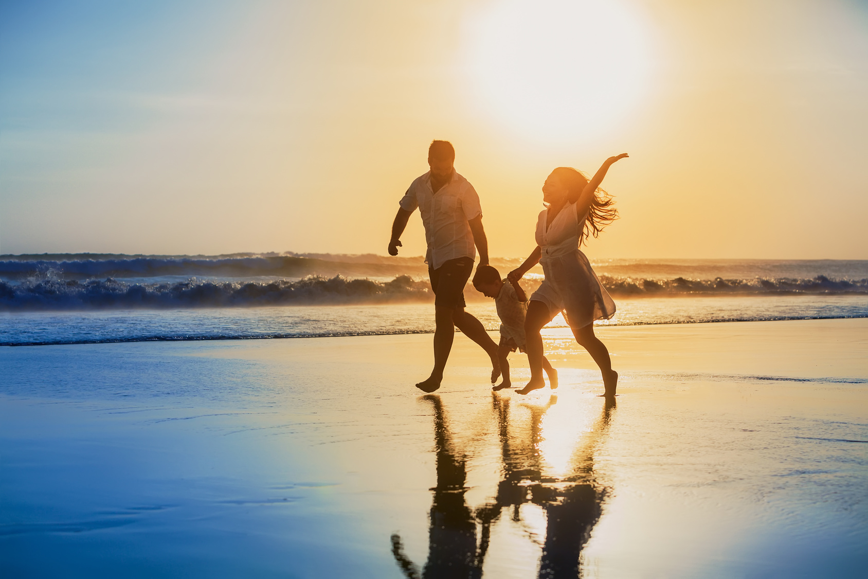 Happy family - father, mother, baby son hold hands and run with fun along edge of sunset sea on black sand beach. Active parents and people outdoor activity on tropical summer vacations with children